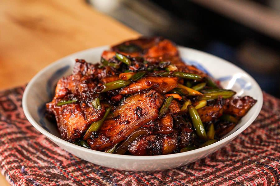 thịt lợn xào trong đĩa, hành lá, đĩa để trên bàn